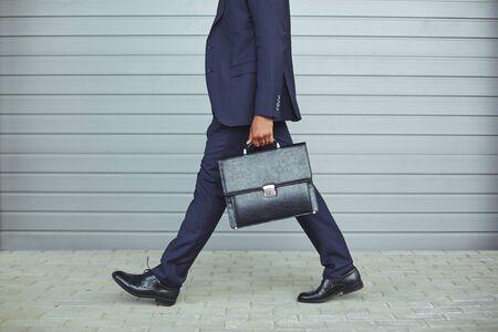 朝、仕事にスーツのビジネスマンの足