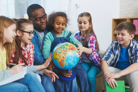 preschoolers: Group of preschoolers looking at globe held by their teacher