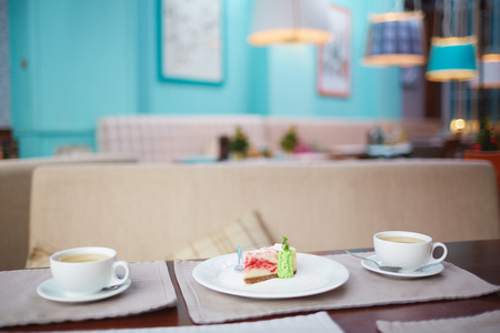 tea table: Two cups of tea and cake on table in cafe Stock Photo