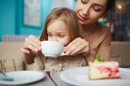 people eating: Young woman helping her little daughter drink tea from cup