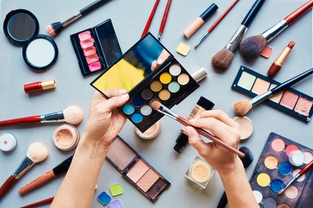 face work: Hands of beautician with shadows over cosmetic products for make-up