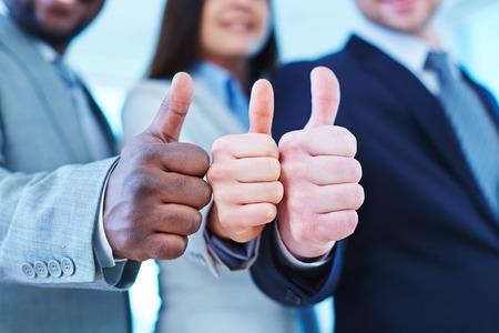 manos juntas: Pulgar arriba gesto muestra por tres socios de negocios