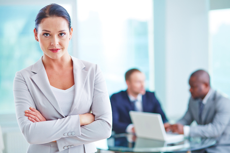 Working Environment: Pretty businesswoman looking at camera in working environment