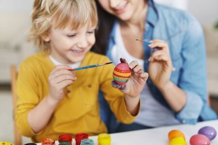 craft: Little boy painting Easter eggs with his mother near by Stock Photo