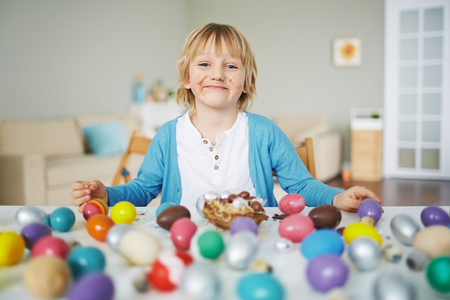 Happy boy looking at camera by Easter table
