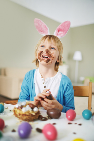 sweettooth: Happy boy with rabbit ears eating chocolate eggs by Easter table Stock Photo