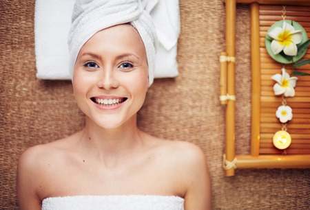 revitalize: Happy girl looking at camera while enjoying aromatherapy