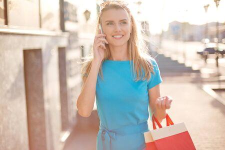 persona feliz: La muchacha bonita con bolsas de papel discutir sus compras en el tel�fono