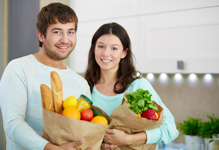 vegs: Young couple with fresh bread and vegs looking at camera Stock Photo
