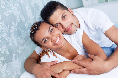 Happy young couple looking at camera with smiles photo