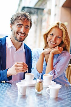 young women: Romantic young couple looking at camera while sitting in cafe Stock Photo