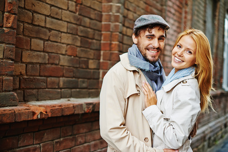 amorous woman: Romantic valentines in trench-coats looking at camera Stock Photo