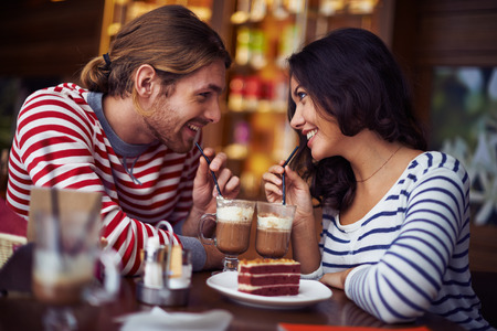 adult valentine: Happy young couple enjoying dessert in cafe Stock Photo