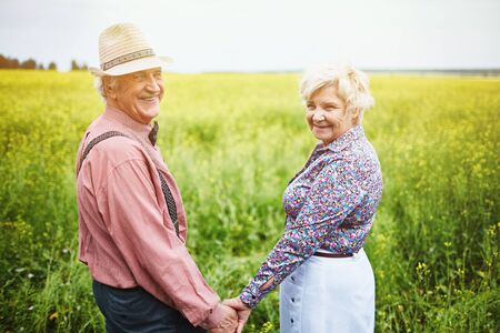 Affectionate seniors holding by hands while standing in meadow