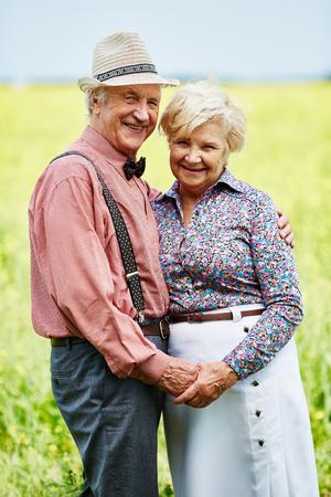 parejas amor: las personas mayores cariñosos que sostienen con las manos en el medio rural