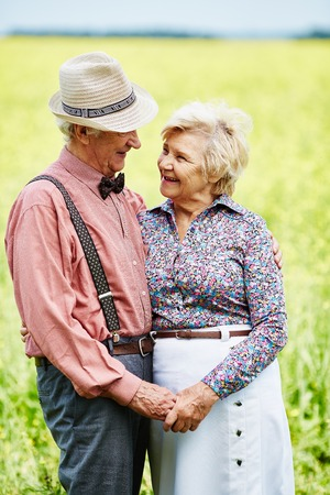 amorous: Amorous seniors looking at one another in blooming meadow