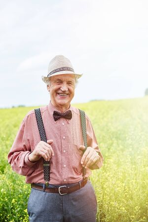welldressed: Happy well-dressed senior man looking at camera in meadow