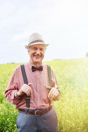 Felice l'uomo anziano ben vestito guardando la fotocamera nel prato