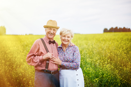 couples outdoors: Happy senior couple looking at camera on the countryside