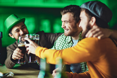 Friendly men toasting with beer in pub Stock Photo