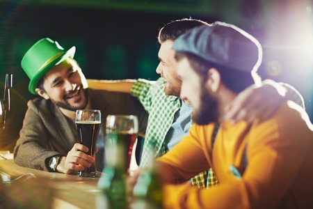 Friendly men drinking beer and talking in pub