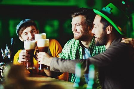 hombre tomando cerveza: Individuos felices con vasos de espuma de cerveza pasar tiempo en el pub