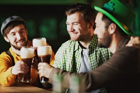 cheers: Happy men spending St. Patrick day in tavern