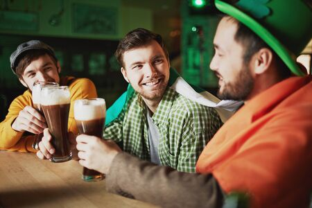 pubs: Cheerful guys with beer and Irish flag sitting in pub Stock Photo