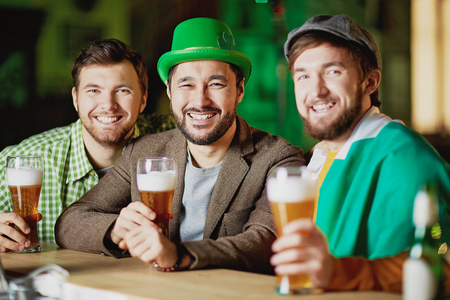 Group of friendly young men having beer on St. Patrick day
