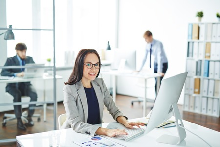 secretaria: Secretaria bonita mirando la cámara en el lugar de trabajo delante del ordenador