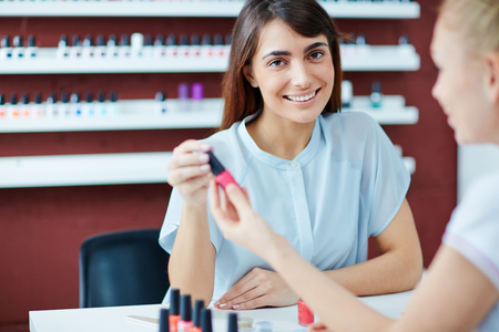 manicurist: Smiling woman looking at camera while visiting her manicurist