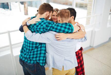grupo de hombres: Grupo de estudiantes que abrazan mientras está de pie en el círculo Foto de archivo