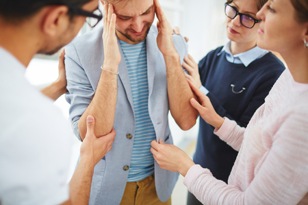 reassure: Group of helpful students supporting depressed guy Stock Photo
