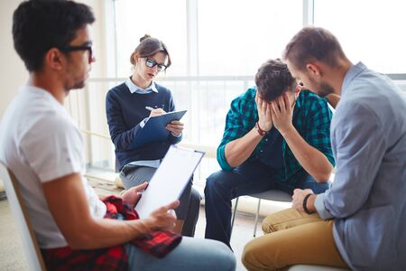 despaired: Group of helpful students supporting their despaired friend