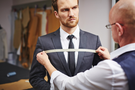 tailor measure: Mature tailor taking measures of businessman jacket