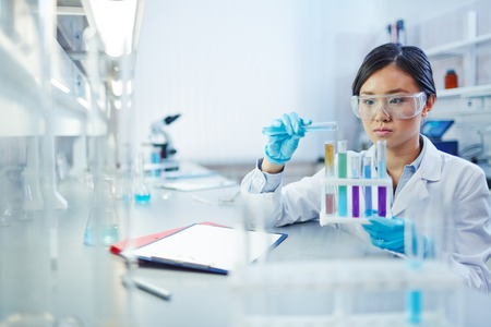 Asistentka analýzu kapalin v nádobách vědeckých laboratoří Reklamní fotografie