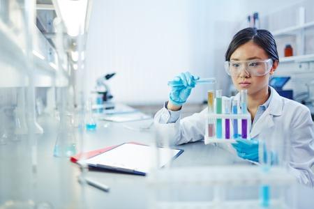 Vrouwelijke assistent analyseren van vloeistoffen in flesjes in wetenschappelijk laboratorium