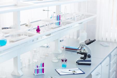 Glassware, microscope and clipboard at workplace in scientific lab