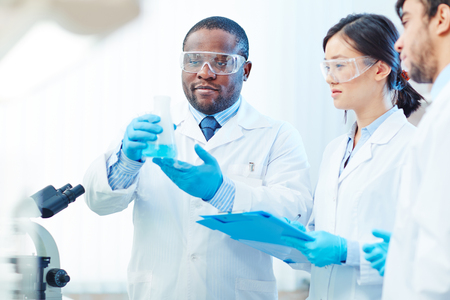scientist man: Group of chemists looking at blue liquid substance in tube Stock Photo