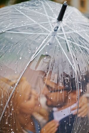 parejas romanticas: San Valent�n rom�nticos que se colocan bajo el paraguas bajo la lluvia Foto de archivo
