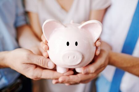 Piggy bank held by business partners Stock Photo