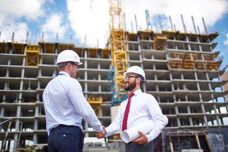 building trust: Two young partners handshaking on background of building structure