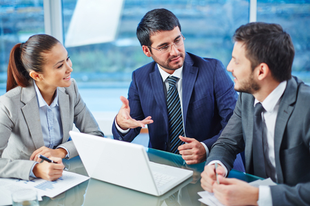 Happy businesspeople explaining colleague the main points of new project Stock Photo