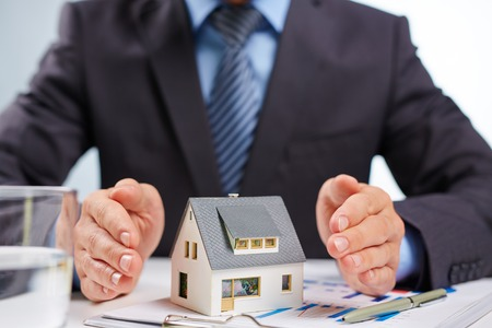 Businessman open palms surrounding toy house Stock Photo