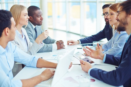 work group: Group of business partners interacting at meeting