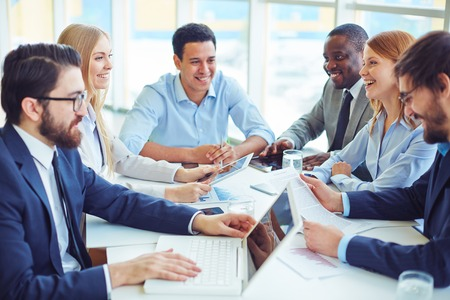 person: Happy business partners voicing their ideas at meeting