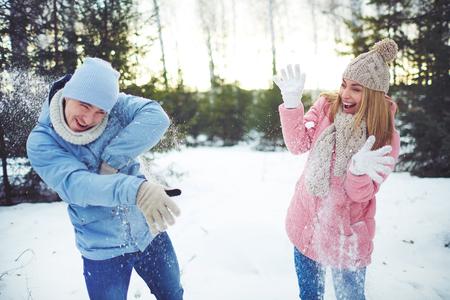palle di neve: Joyful palle di neve coppie che giocano in parco