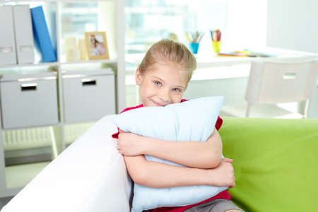 Cute little girl with pillow looking at camera photo