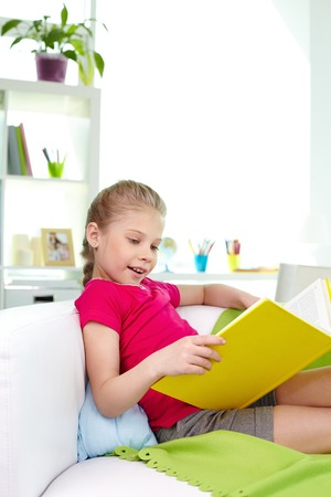 Cute little girl reading book at home photo