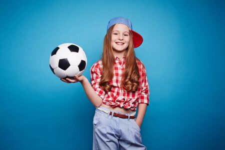 child ball: Happy girl in casualwear holding ball for playing football Stock Photo